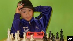 Maximillian Lu adjusts his cap as he toys with a chess set during an interview, Nov. 16, 2015, in Armonk, N.Y. The 10-year-old recently became the youngest chess master ever in the United States.