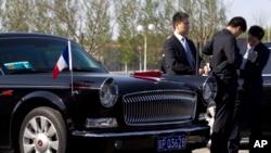 在北京首都机场,警卫人员守卫在一辆准备迎接法国总统奥朗德的红旗牌轿车旁。(2013年4月25日资料照)