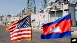 FILE: Cambodian and U.S. national flags flutter at Sihanoukville port, as the guided missile grigate USS Gary is docked in the background in Sihanoukville, some 185 kilometers (115 miles) southwest of Phnom Penh, Cambodia's capital, Friday, Feb. 9, 2007. The U.S. navy warship docked at Cambodia's main sea port Friday in its first visit in more than three decades to the impoverished Southeast Asian nation. (AP Photo/Heng Sinith)