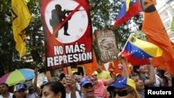Manifestantes portan carteles durante una marcha antigubernamental este sábado en Caracas.