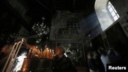 Giáo dân đốt nến trong nhà thờ Giáng Sinh ở Bethlehem