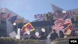 藏人在洛杉磯湖人隊的史鐵波斯中心前高舉美國和西藏旗幟示威﹐紀念抗暴。(視頻截圖)
