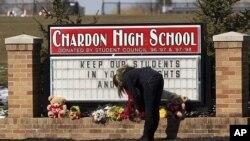 美国俄亥俄州查尔顿高中星期一发生枪击案,一名学生在校门前放鲜花。
