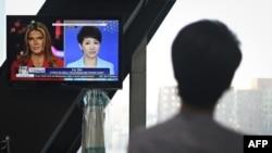 中国环球电视网主播刘欣在北京的央视总部观看她自己与美国福克斯商业频道主播翠西·里根进行电视辩论的录像。(2019年5月30日)