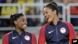 FILE - In this Aug. 9, 2016, file photo, U.S. gymnasts and gold medallists, Simone Biles, left and Gabrielle Douglas celebrate on the podium during the medal ceremony for the artistic gymnastics women's team at the 2016 Summer Olympics in Rio de…