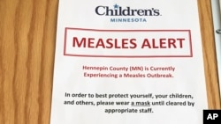 A sign at the specialty clinic at Children's Minnesota in Minneapolis alerts patients to a measles outbreak in the area, May 2, 2017. In interviews with Somali mothers in Minnesota, VOA's Somali Service found that anti-vaccine views are widespread.