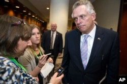 National Governors Association (NGA) Chairman Gov. Terry McAuliffe speaks with reporters after leaving a health care reform meeting during the NGA's Winter Meeting in Washington, Saturday, Feb. 25, 2017.