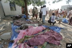 People stand near bodies of people who were killed at the al-Zaydiya security headquarters, that was destroyed by Saudi-led airstrikes Saturday, in the Red Sea port city of Hodeida, Yemen, Oct. 30, 2016.