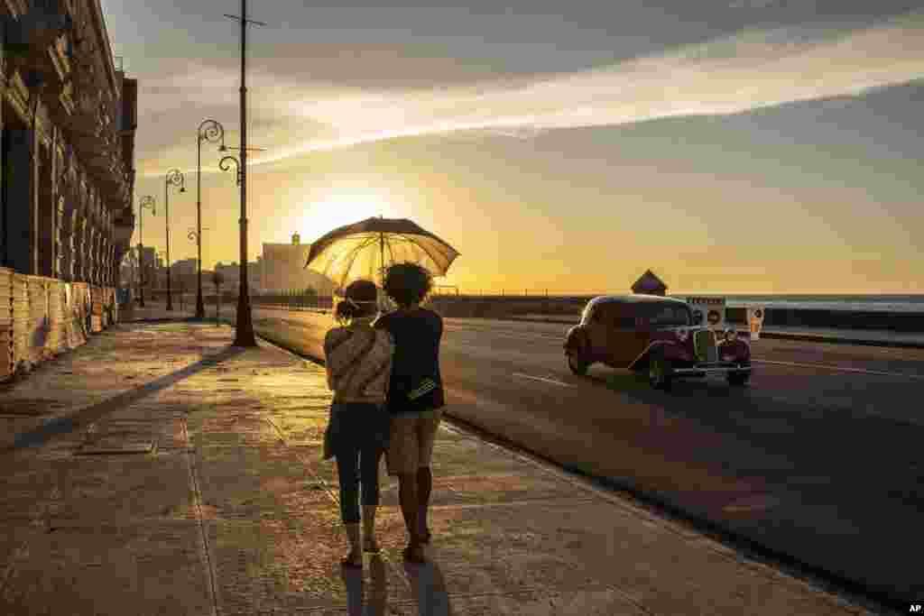 A couple walks on the Malecon seawall at sunset in Havana, Cuba, Aug. 31, 2020.