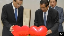 China's Premier Li Keqiang, left, pulls a symbol of China-Cambodia Heart Journey, together with his Cambodian counterpart Hun Sen, center, during a signing ceremony at Peace Palace in Phnom Penh, Cambodia, Thursday, Jan. 11, 2018. Cambodia and China on Th