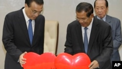 China's Premier Li Keqiang, left, pulls a symbol of China-Cambodia Heart Journey, together with his Cambodian counterpart Hun Sen, center, during a signing ceremony at Peace Palace in Phnom Penh, Cambodia, Thursday, Jan. 11, 2018.