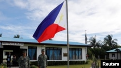 FILE - Filipino soldiers stand at attention near a Philippine flag at Thitu island in disputed South China Sea, April 21, 2017.