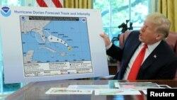 "Presiden AS Donald Trump memegang gambar mengenai perkiraan lintasan badai Dorian yang ditambah sendiri dengan ""kemungkinan melintasi negara bagian Alabama"" di Gedung Putih, Rabu (4/9)."
