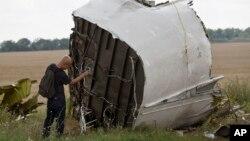 Малазийский следователь делает фотографии обломков малазийского авиалайнера рейса МН-17 на месте падения самолета в Украине. 22 июля 2014 г.