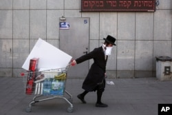 FILE - An ultra-Orthodox Jew wears an improvised protective face mask as he pulls a supermarket cart on a mainly deserted street because of the government's measures to help stop the spread of the coronavirus, in Bnei Brak, a suburb of Tel Aviv.