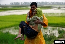 A local man carries an old Rohingya refugee woman as she is unable to walk after crossing the border, in Teknaf, Bangladesh, Sept. 1, 2017.