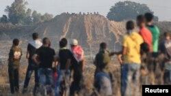 2015年10月以色列和加沙地带边界附近的冲突期间,巴勒斯坦抗议者注视掩护在沙丘后面的以军士兵。