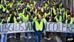 "Yellow Vests (Gilets jaunes) march behind a banner reading ""Yellow vests are angry"" as they protest high fuel prices in Rochefort, southwestern France, Nov. 24, 2018, part of a movement which has spread into a widespread protest against stagnant spending"