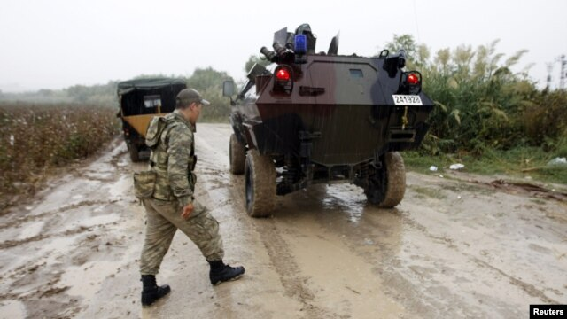 FILE - Turkish soldiers in a military vehicle patrol the Turkish-Syrian border near the village of Hacipasa in Hatay province, Oct. 11, 2012.