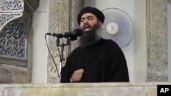FILE - This image from video posted in July purports to show Islamic State leader Abu Bakr al-Baghdadi delivering a sermon in Iraq.