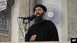 "FILE - This image from video posted in July purports to show Islamic State leader Abu Bakr al-Baghdadi delivering a sermon in Iraq; he's said to have been wounded with British national ""Jihadi John"" in an airstrike last Saturday."