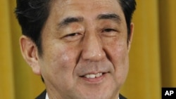 Japan's Liberal Democratic Party President Shinzo Abe smiles during a question and answer during a press conference at the party headquarters in Tokyo, December 17, 2012.