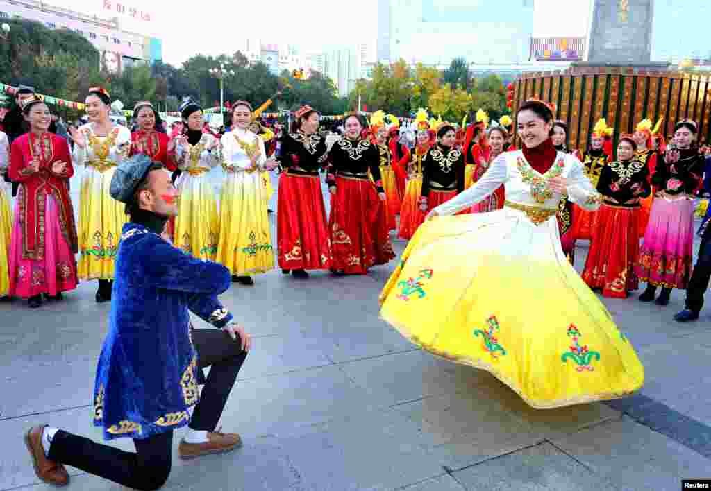 People perform at a square during a celebration on the 60th anniversary of the founding of the Xinjiang Uighur Autonomous Region, in Urumqi.