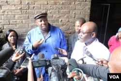 Zimbabwe's Health Minister David Parirenyatwa (right, with glasses), accompanied by local minister Saviour Kasukuwere, talks to journalists after visiting Mbare township, the epicenter of the current typhoid outbreak in Harare, Jan. 2017 (S. Mhofu/VOA). Parirenyatwa has called the lack of hygiene shocking and deplorable.