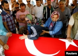 Relatives of Gulsen Bahadir, a victim of Tuesday's attack on Ataturk airport, mourn at her flag-draped coffin during her funeral ceremony in Istanbul, Turkey, June 29, 2016.