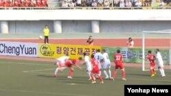 조선중앙TV가 지난 16일 방송한 북한과 우즈베키스탄의 축구 경기 모습. 골대 뒷편 측면으로 북한 기업들의 광고판이 보이다.