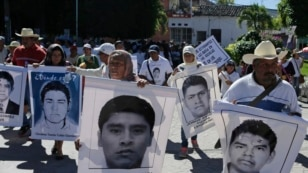 Relatives hold pictures of missing students of the Ayotzinapa Teacher Training College during a protest march demanding the government find them, in Zumpango, in the southern Mexican state of Guerrero, Nov. 27, 2014.