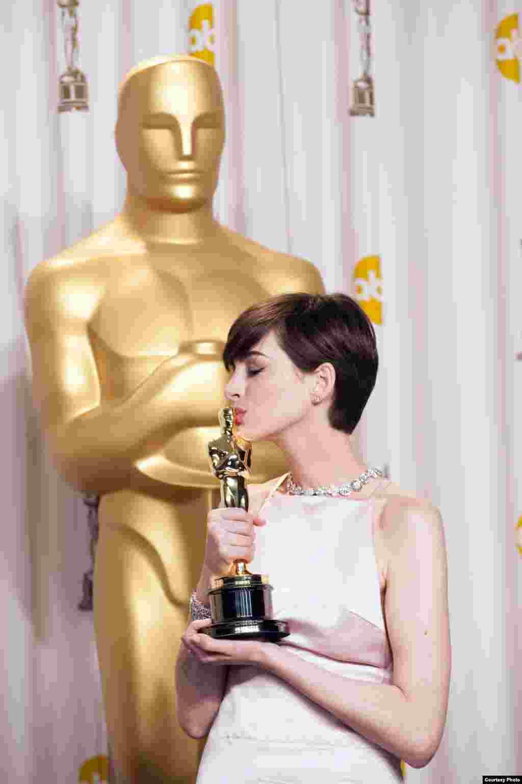 """""""Səfillər"""" filmində ən yaxşı aktrisa kateqoriyasında mükafat aldıqdan sonra Anne Hathaway səhnə arxasında Oskarı jurnalistlərə göstərir. (Foto: Heather Ikei / AMPAS)."""