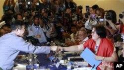 រដ្ឋមន្រ្តីក្រសួងអយស្ម័យយាននិងមេដឹកនាំចរចាខាងរដ្ឋាភិបាល Aung Min (ខាងឆ្វេង) ចាប់ដៃលោកស្រី Naw Si Pho Ra Sein (ខាងស្តាំ) អគ្គលេខាធិការសហភាពជាតិការ៉ែនក្នុងអំឡុងពេលនៃការចរចាសន្តិភាពនៅក្នុងទីក្រុង Yangon ភូមា ថ្ងៃសុក្រ ទី