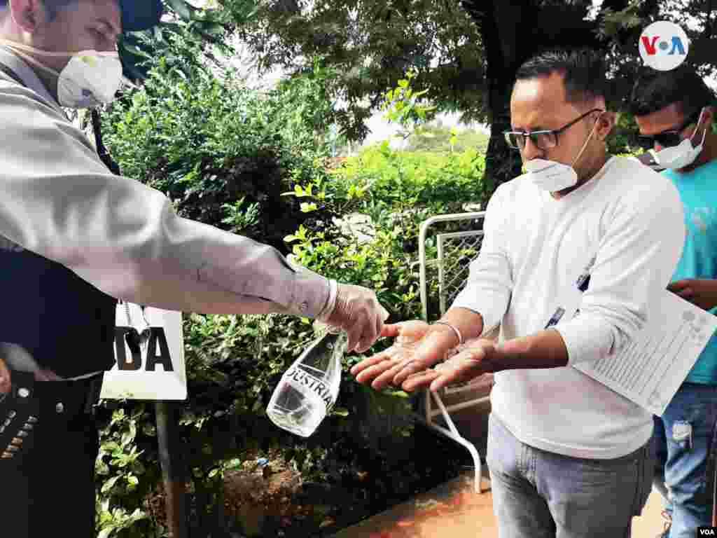 Personal sanitario limpia las manos de un migrante con un gel antibacterial para desinfectar.