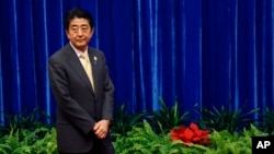 FILE - Japan's Prime Minister Shinzo Abe wait to meet China's President Xi Jinping, during their meeting at the Great Hall of the People, on the sidelines of the Asia Pacific Economic Cooperation (APEC) meetings, in Beijing, Nov. 10, 2014.