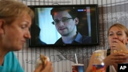 Transit passengers eat at a cafe with a TV screen with a news program showing a report on Edward Snowden, Sheremetyevo airport, Moscow, June 26, 2013.