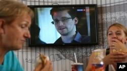 Pasaje ki an tranzit ap manje nan yon bar-restoran nan ayewopò Sheremetyevo nan Moskou, kote yon chèn televizyon montre yon pòtre Edward Snowden.