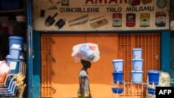 Un homme avec sa marchandise sur sa tête passe devant un magasin fermée au Marché Central, à Kinshasa, le 8 juillet 2016.