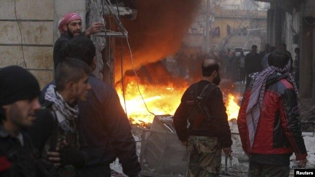 Chiến binh phe nổi dậy đứng cạnh một địa điểm bị cháy, vì đạn pháo của lực lượng chính phủ, trong thành phố Aleppo của Syia, 3/1/13