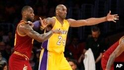 Kobe Bryant (No. 24, an jonn sitwon) tap tann yon pas pandan yon lòt gwo vedèt NBA a, LeBron James, tap make li nan yon match ki tap dewoule nan Los Angeles nan dat 10 mas 2016 la. (Foto: Danny Moloshok/AP).