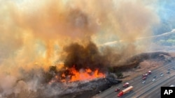 In this photo released by the Los Angeles County Fire Department Air Operations traffic passes the Route fire, a brush wildfire off Interstate 5 north of Castiac, Calif., on Sept. 11, 2021.
