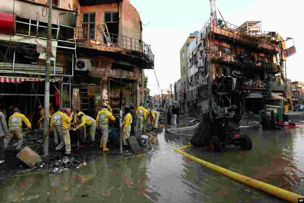 Baghdad municipality workers clean up debris after a car bomb attack, Baghdad, Iraq, Feb. 18, 2014.
