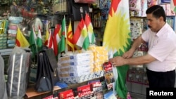 FILE - A Kurdish man sells flags of the semi-autonomous region of Kurdistan in his shop in Arbil, 310 km (193 miles) north of Baghdad, Aug. 30, 2009.