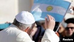 El papa Francisco saluda en dirección de una bandera argentina a su llegada a la audiencia semanal en la Plaza de San Pedro, en el Vaticano.