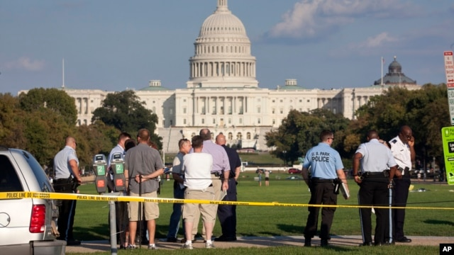 Law enforcement officers are near the scene on the National Mall in Washington, where, according to a fire official, a man set himself on fire, Oct. 4, 2013.
