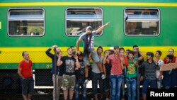 Adnan Shanan (tengah) seorang pengungsi dari Latakia di Suriah, ikut protes di depan kereta di stasiun kereta api Bicske, Hungaria, 4 September 2015.