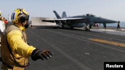Flight deck crew member confirms the deck is all clear before a F/A-18C Hornet of Strike Fighter Squadron (VFA-87) take offs the aircraft carrier USS George H.W. Bush (CVN 77), in the Gulf August 12, 2014.