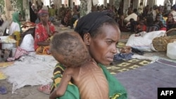 Сомалійська жінка з дитиною із симптомами недоїдання