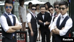 FILE - Ling Jueding (C) poses for a photo with his best men before his wedding ceremony at a park in Beijing, June 27, 2015.