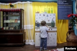 A child observes objects that make up part of a communist-era interior inside the newly opened Kitsch Museum in Bucharest, Romania, May 5, 2017.